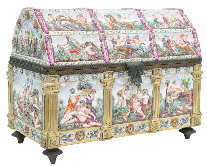 Exuberante e rara caixa para jóias de porcelana ricamente policromada e dourada. Marca de manufatura Capodimonte – Nápoles. Esta com grandes dimensões na forma de baú. Guarnições de metal dourado. 30 x 54 x 20 cm